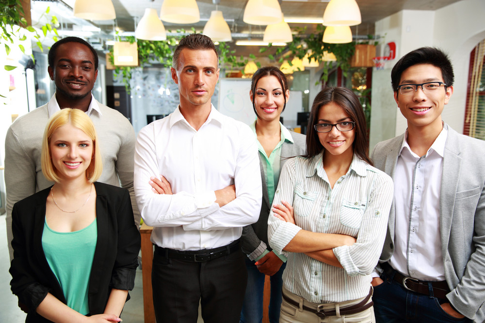 Group of a smiling businesspeople standing together in office