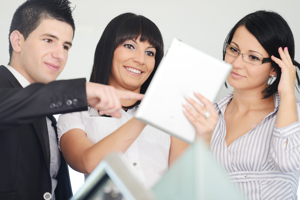 Group of business people using tablet computer in office