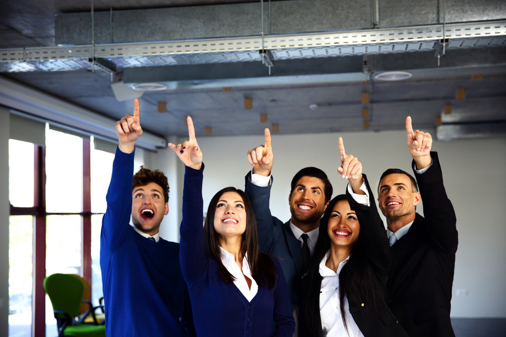 Group of cheerful business people pointing up