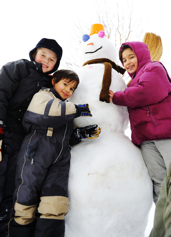 Group of children playing happily in snow making snowman, winter season
