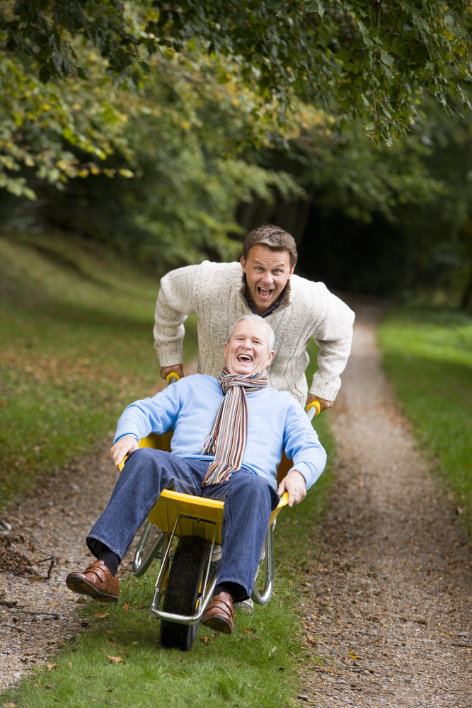 Grown Up Son Pushing Father In Wheelbarrow Along Track