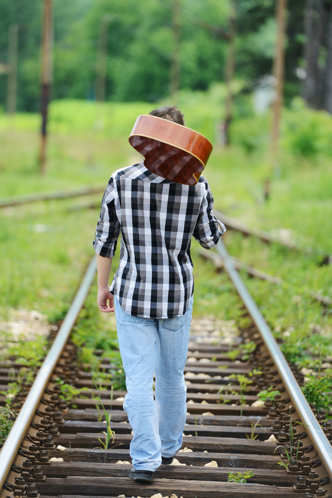Guy carrying guitar on a railway