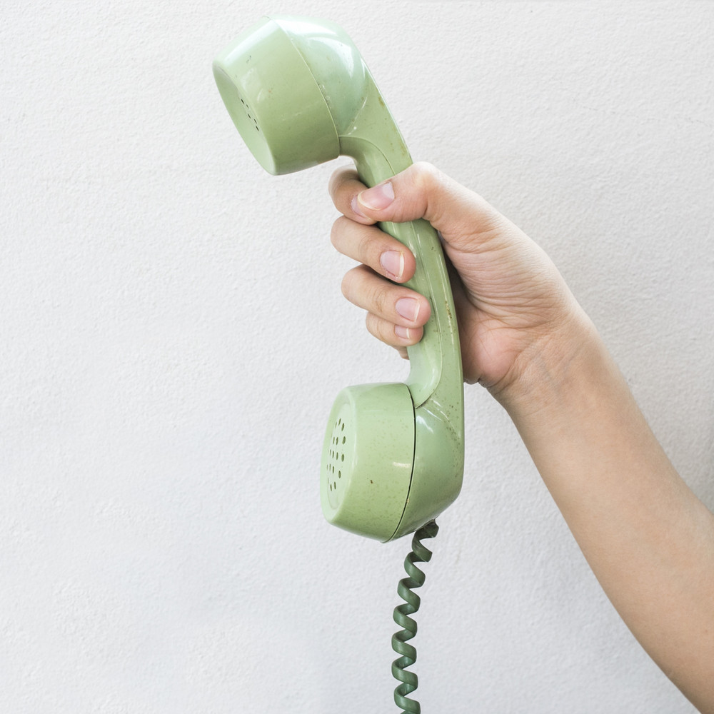 Hand hold vintage telephone green color on white wall background