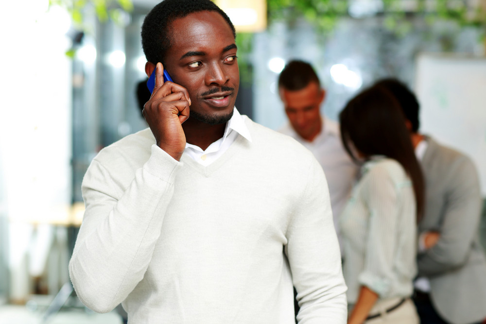 Handsome african businessman talking on the smartphone in front of colleagues