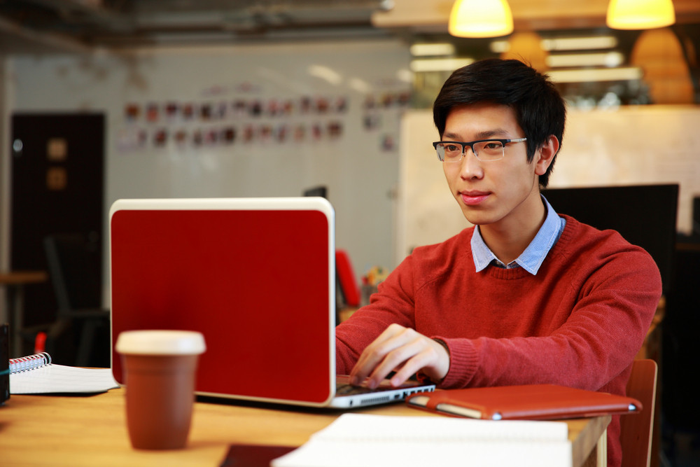 Handsome asian man in glasses working on laptop in office