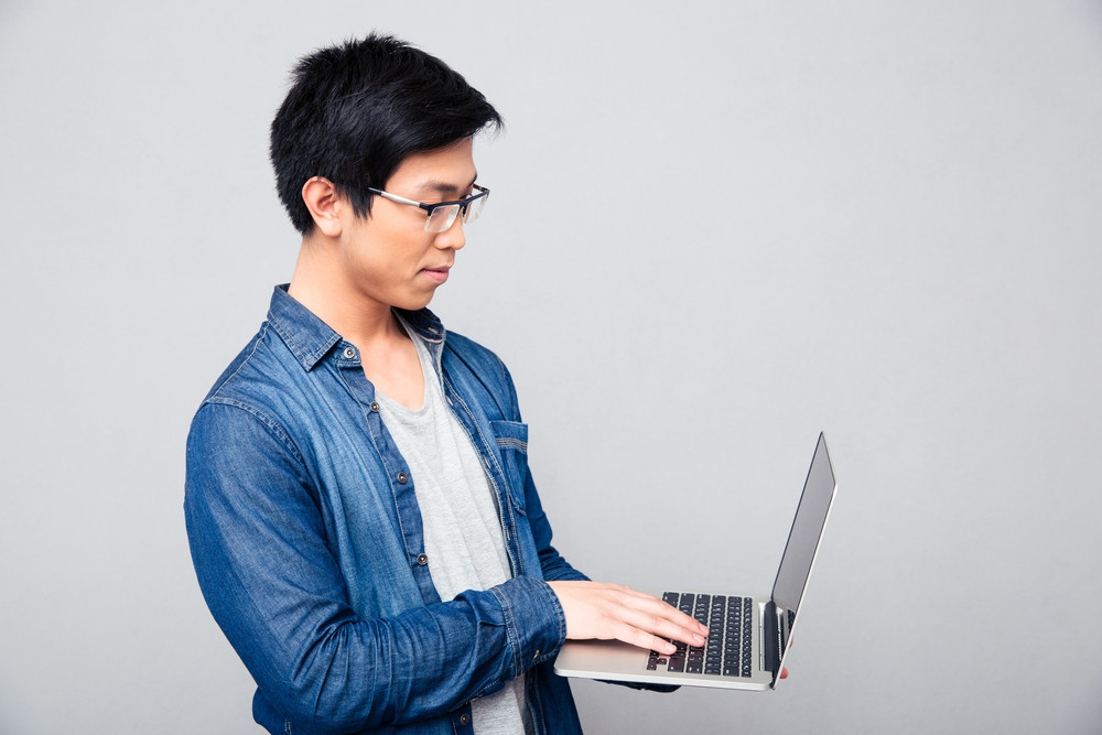 Handsome asian man using laptop