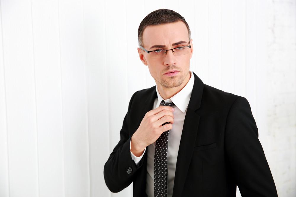 Handsome businessman in glasses adjusting his tie