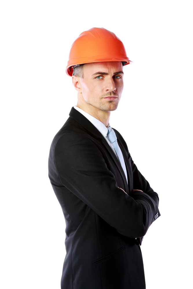 Handsome businessman in helmet standing with arms folded over white background
