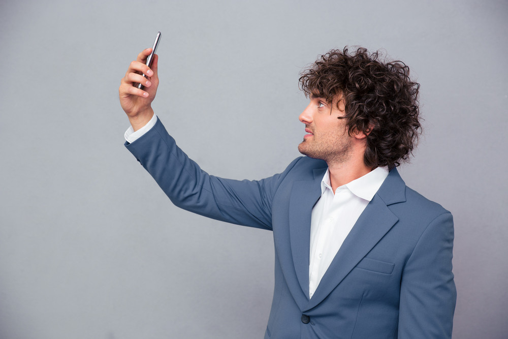 Handsome businessman making selfie photo