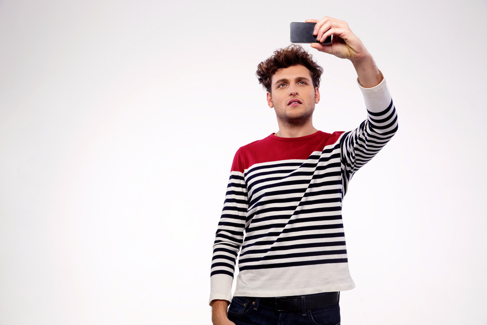 Handsome casual man making selfie photo over gray background