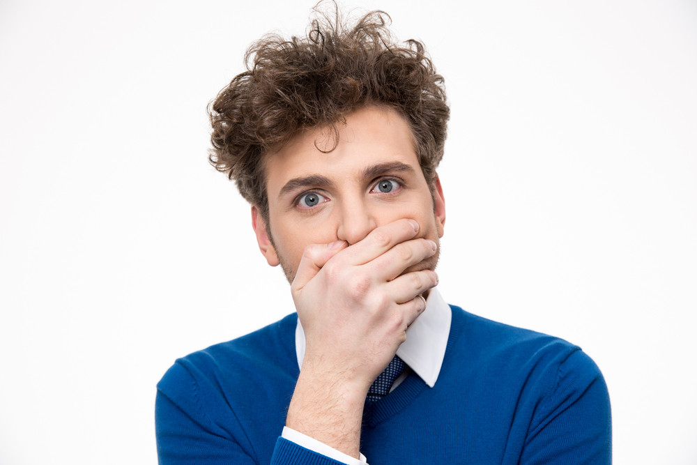 Handsome man covering his mouth over white background