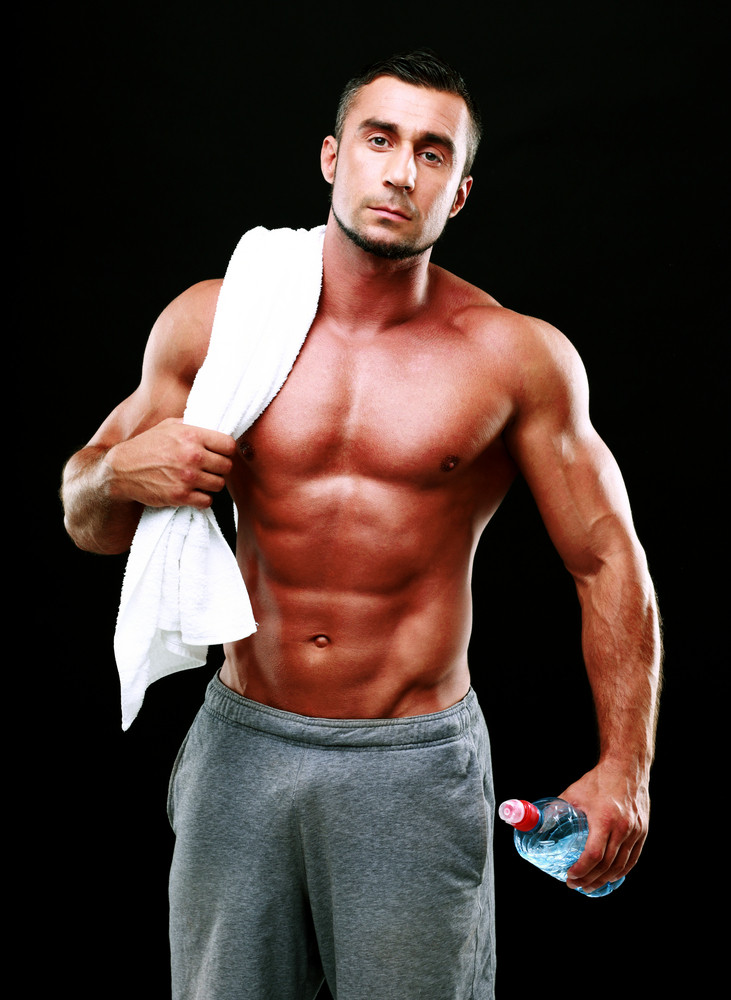 Handsome muscular man holding towel and bottle with water on black background