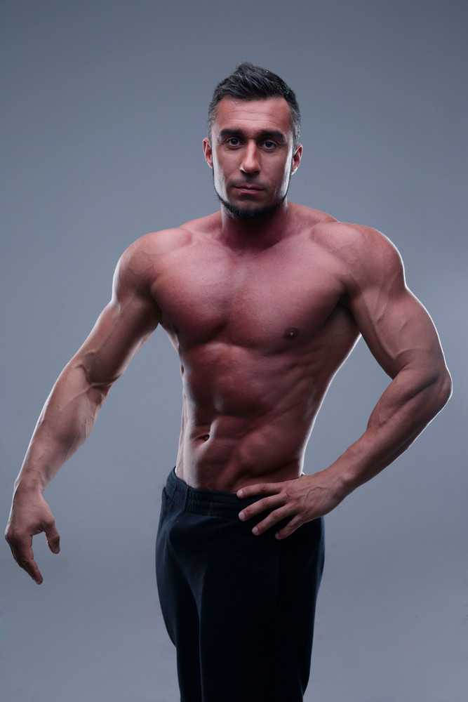 Handsome muscular man standing over gray background
