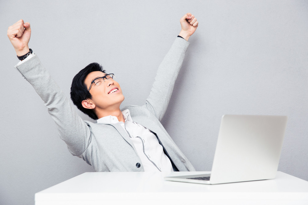 Happiness businessman sitting at the table with laptop