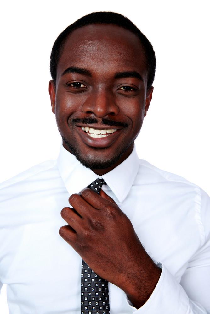 Happy african man adjusting his necktie over white background