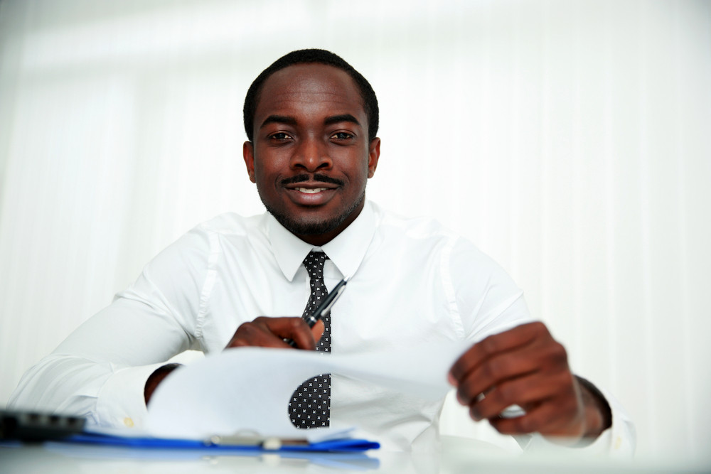 Happy african man sitting at the table and signing document in office