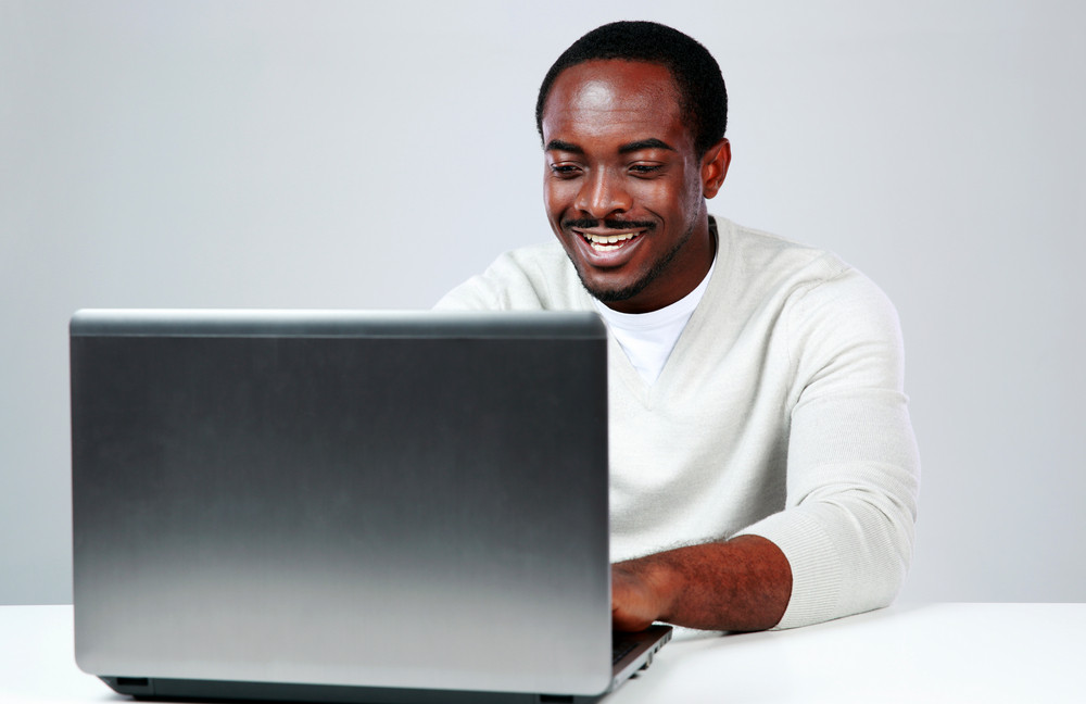 Happy african man sitting at the table and using laptop on gray background