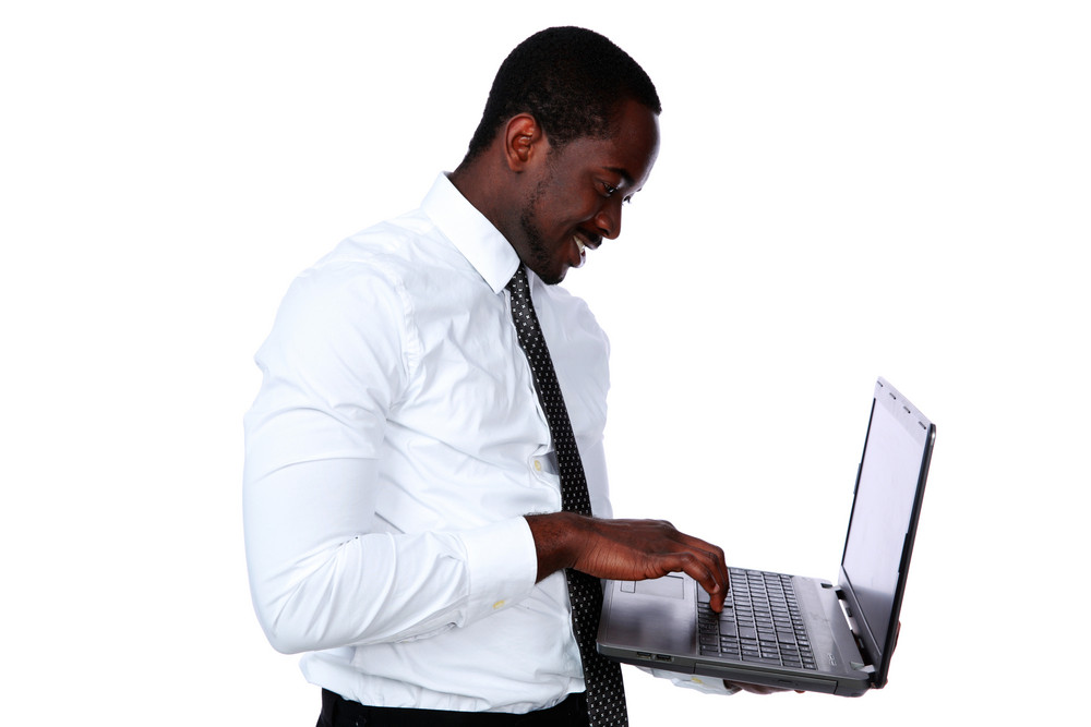 Happy african man standing and using laptop over white background