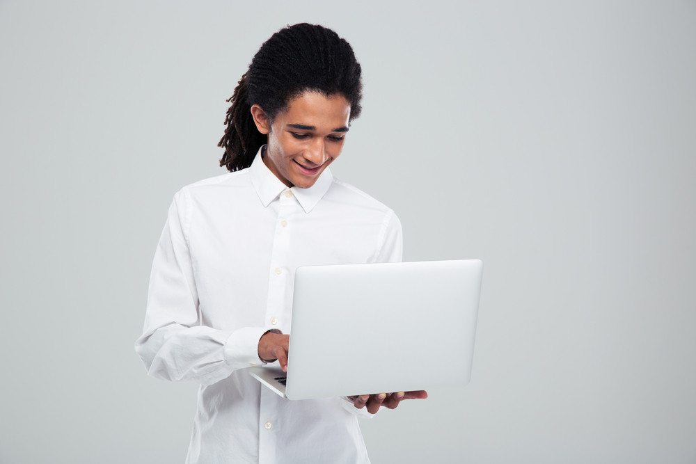 Happy afro american businessman using laptop over gray background