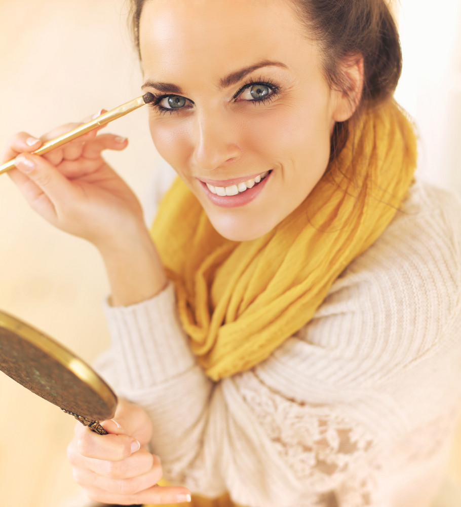 Happy and confident woman putting makeup on