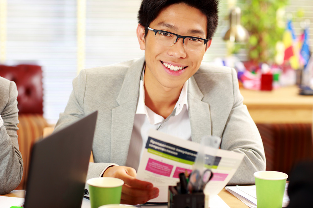 Happy asian businessman in glasses sitting at the table and holding document in office