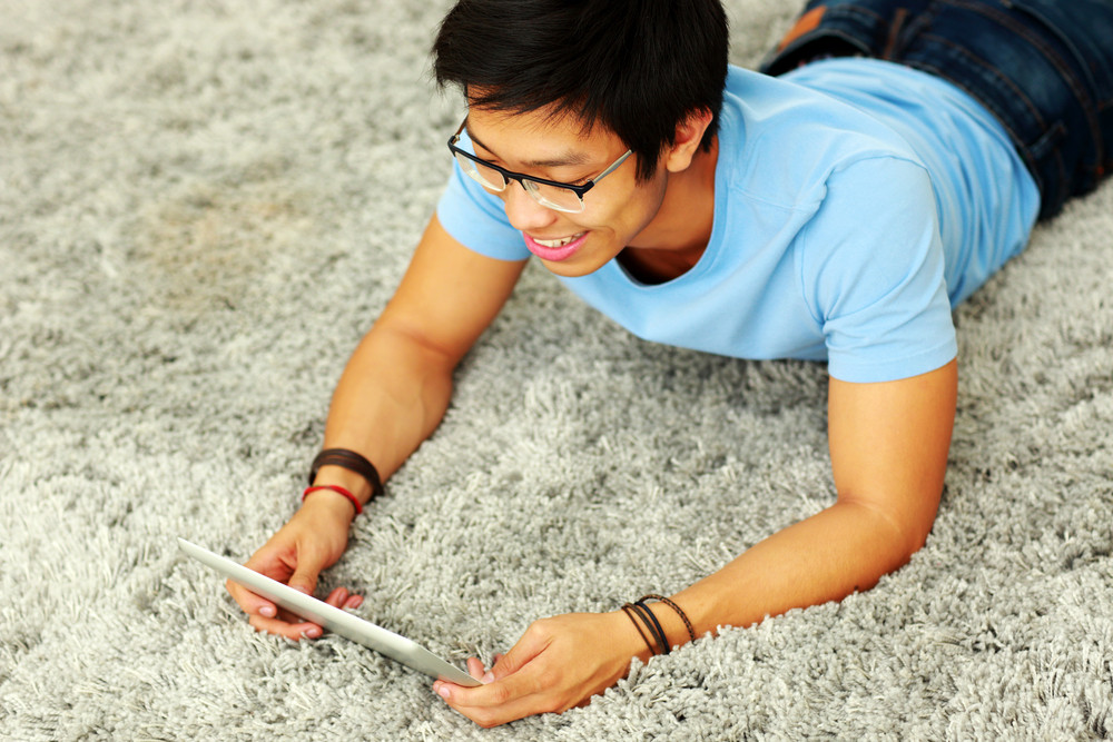 Happy asian man lying on the carpet with tablet computer