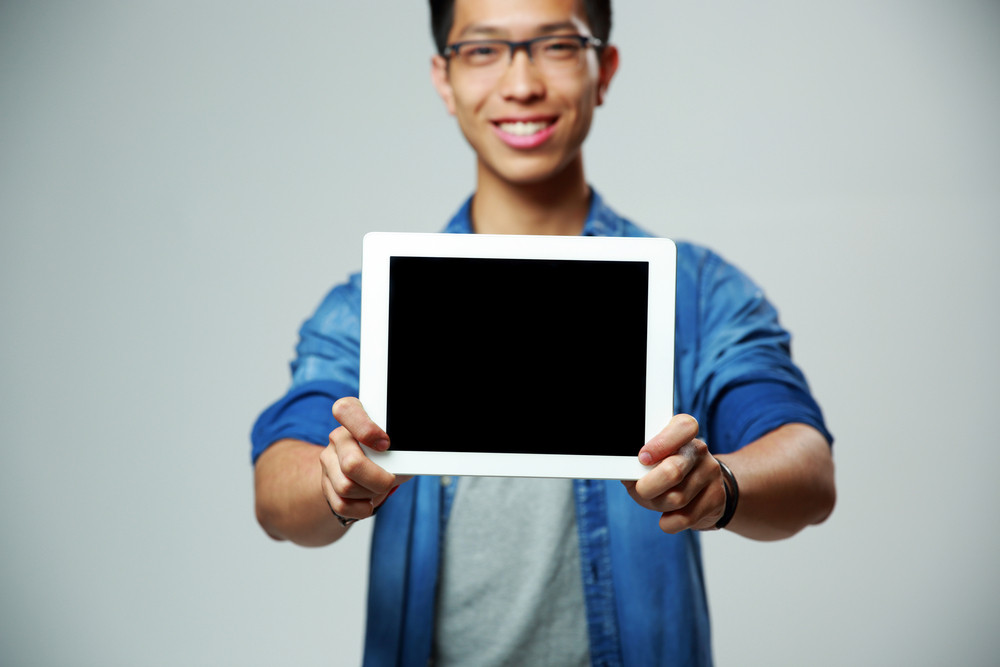 Happy asian man showing tablet computer screen on gray background. Focus on tablet computer