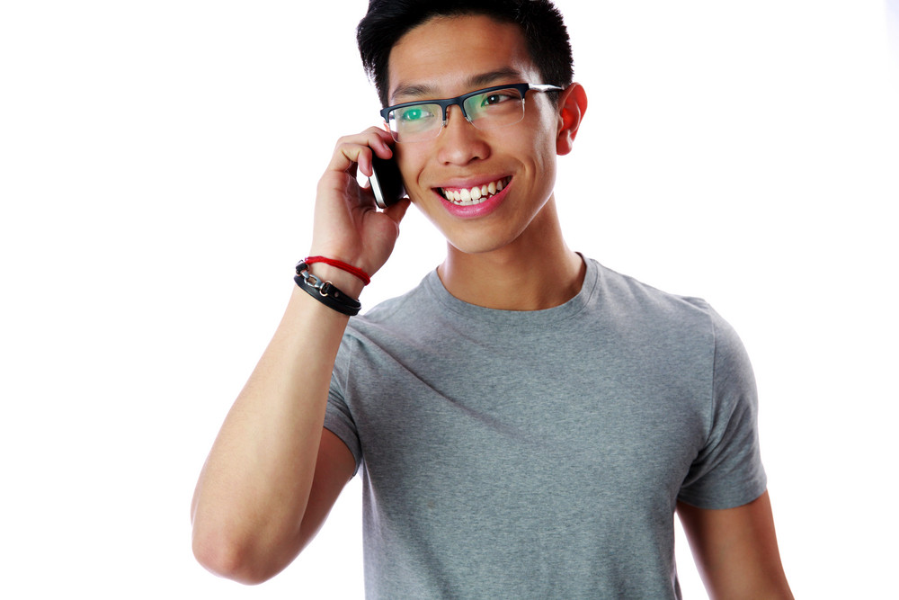 Happy asian man talking on the phone over white background