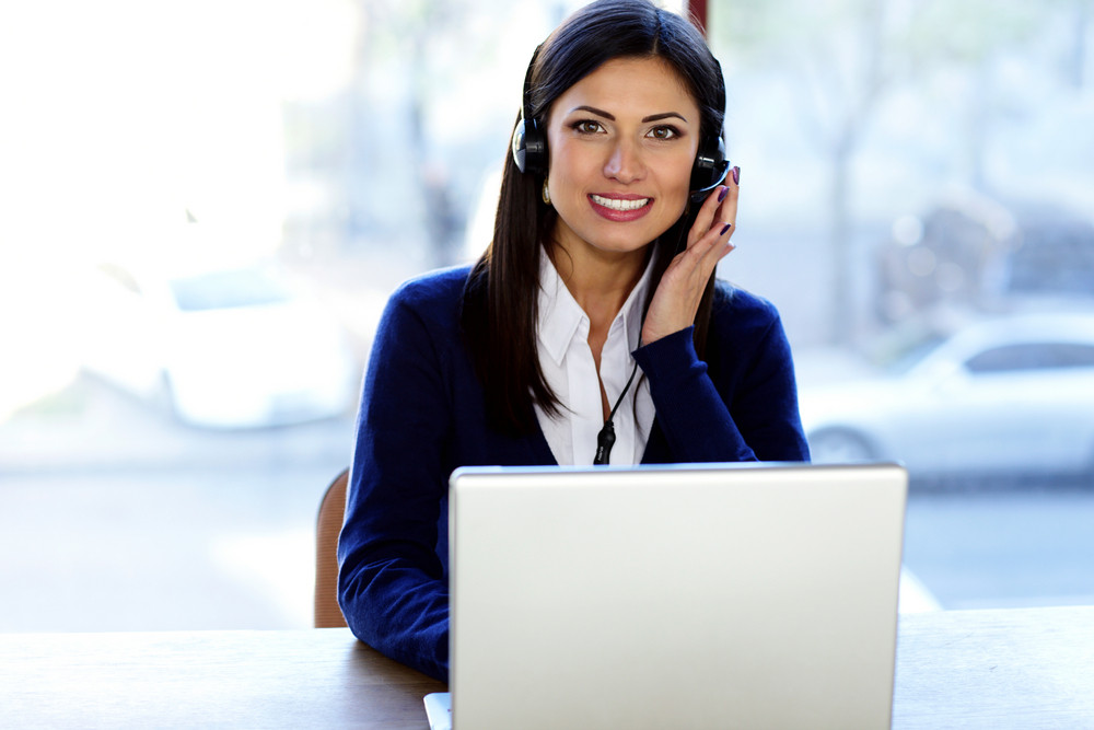 Happy beautiful call-center assistant at the desk