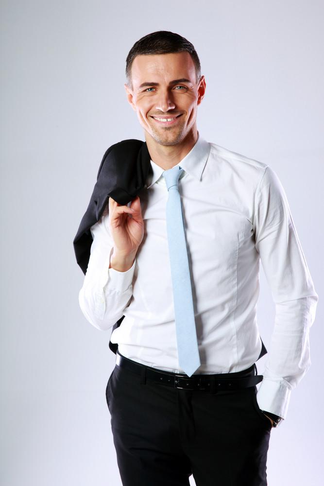 Happy business man holding jacket on shoulder on gray background
