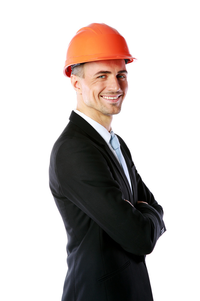 Happy businessman in helmet with arms folded over white background
