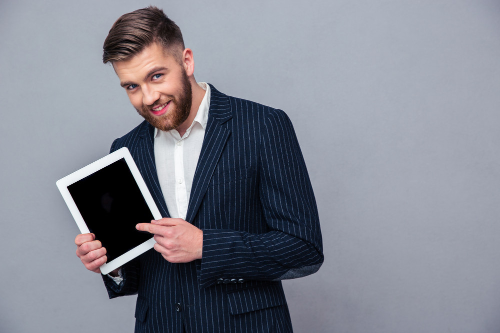 Happy businessman showing tablet computer screen