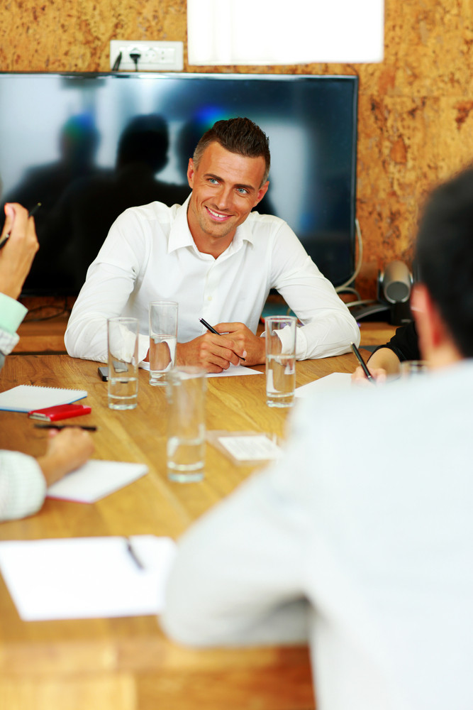 Happy businessman sitting at the meeting in office