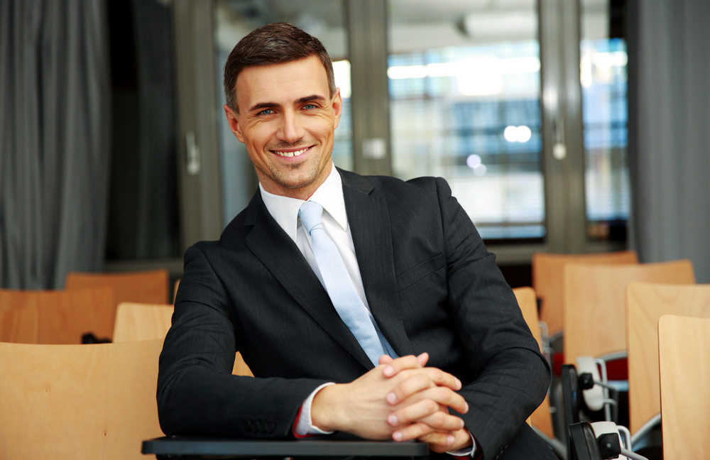Happy businessman standing at conference hall