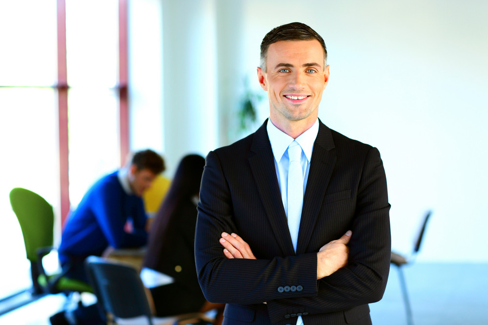 Happy businessman standing with arms folded in front of colleagues