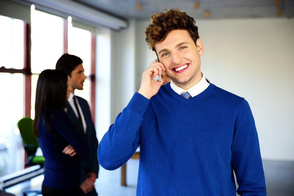 Happy businessman talking on the phone in office