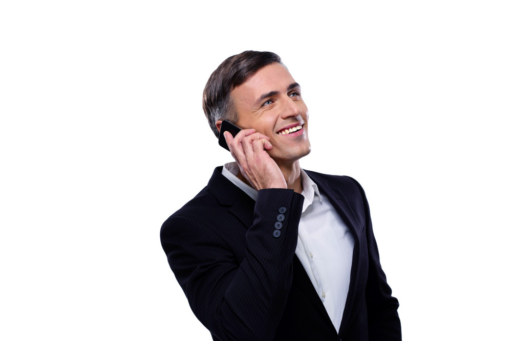 Happy businessman talking on the phone over white background