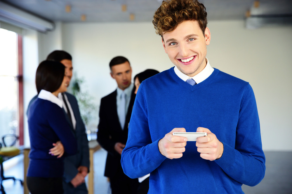 Happy businessman using smartphone in front of a colleagues
