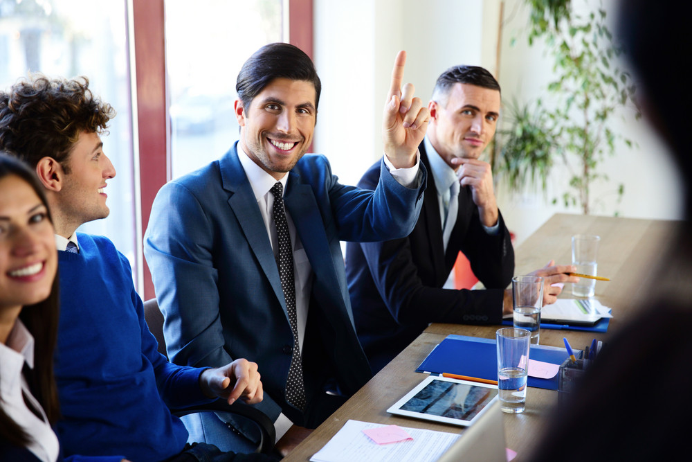 Happy businesspeople sitting at the table in a meeting