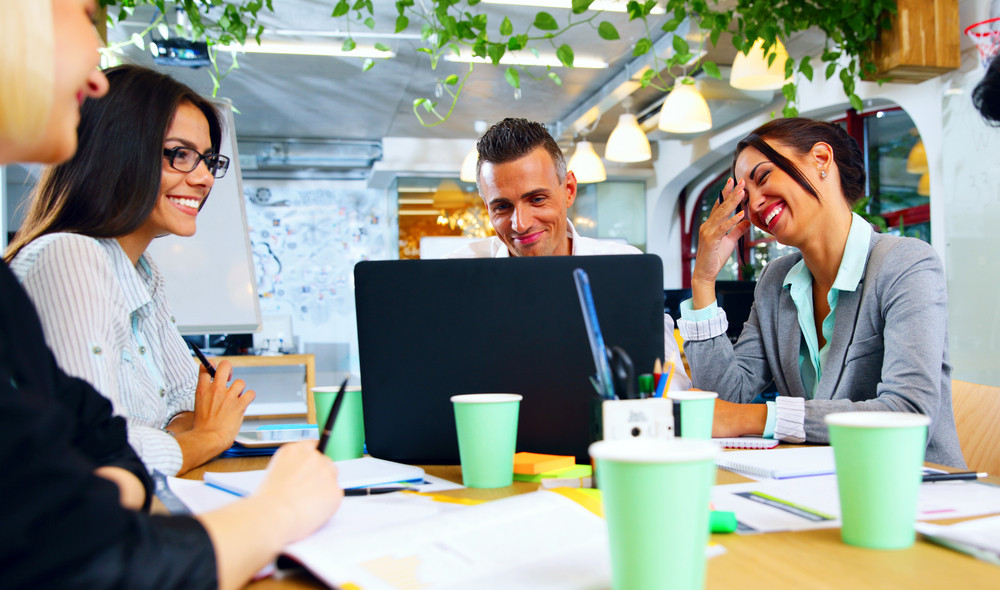 Happy businesspeople working together around the table in office