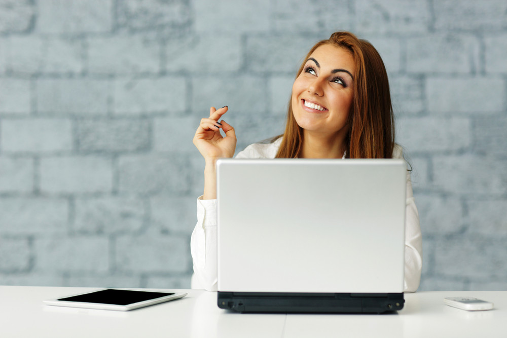 Happy businesswoman sitting at the table in office and pointing up
