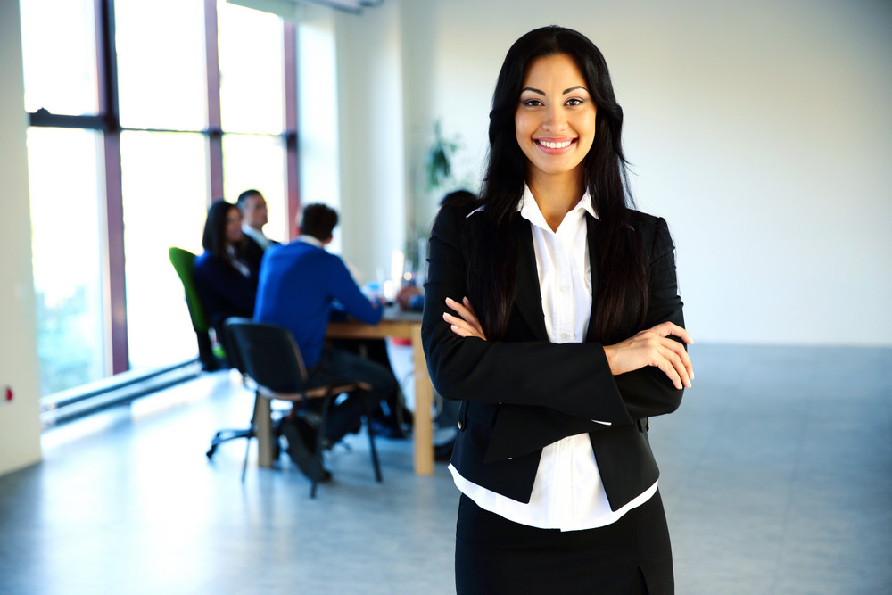 Happy businesswoman standing in front of a business meeting