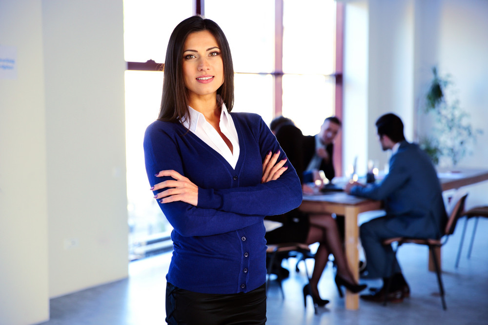 Happy businesswoman standing with arms folded in front of colleagues