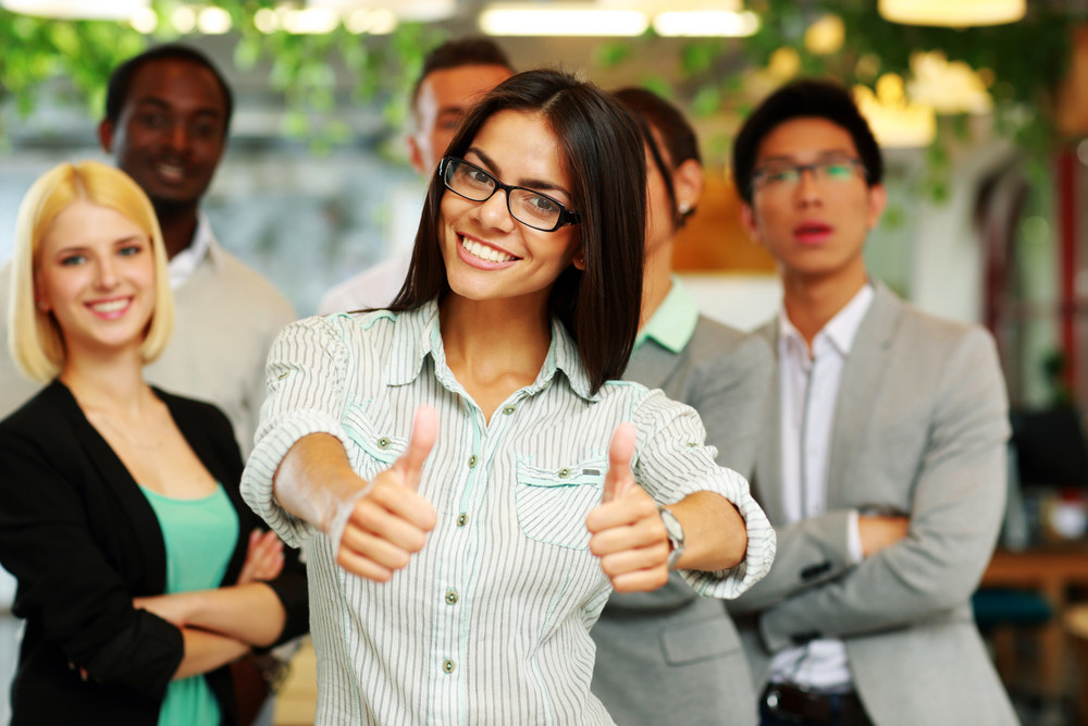 Happy businesswoman standing with thumbs up in front her colleagues