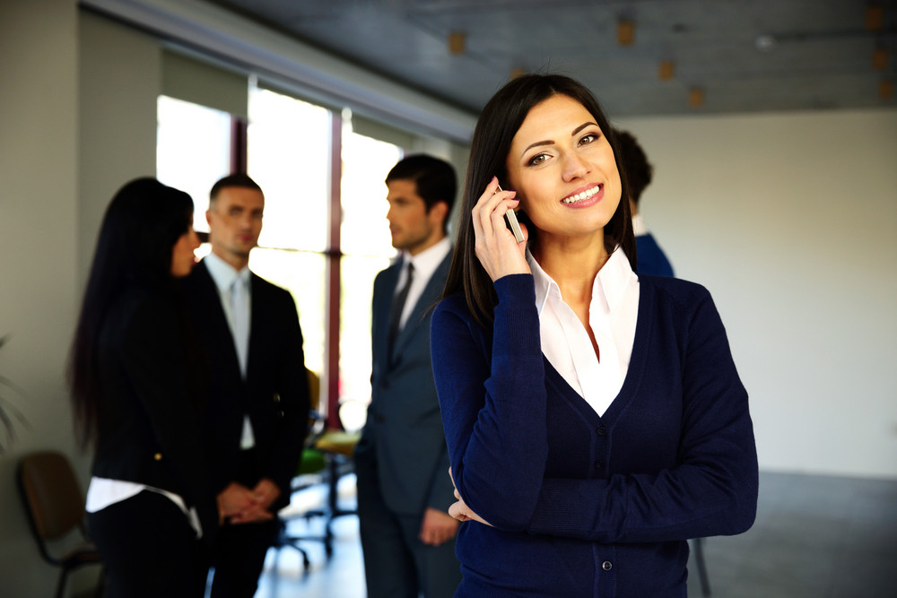 Happy businesswoman talking on the phone with colleagues on background