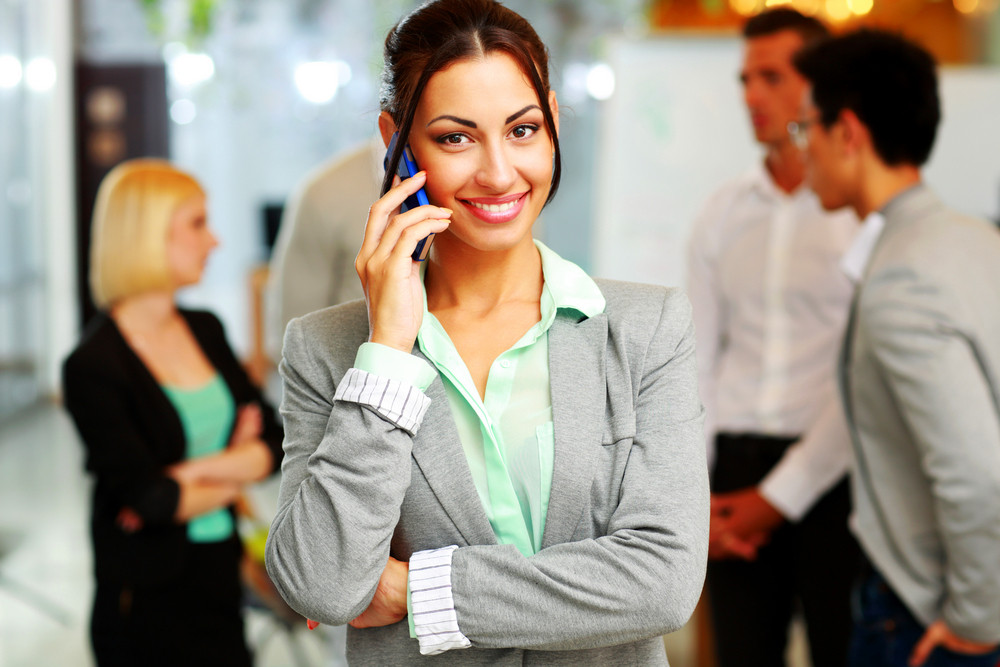 Happy businesswoman talking on the smartphone in front of colleagues