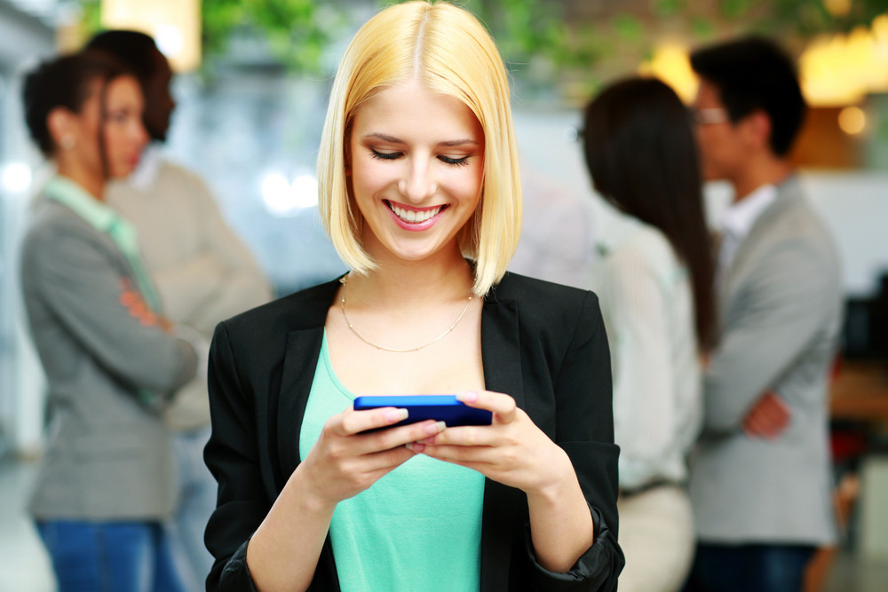 Happy businesswoman using smartphone in front of colleagues