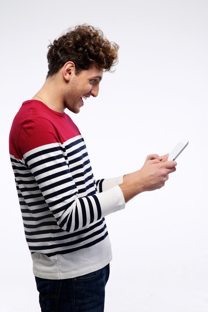 Happy casual man using tablet computer over gray background