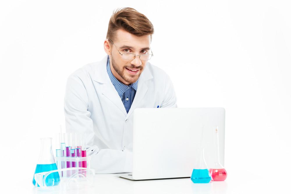 Happy chemist using laptop computer in laboratory