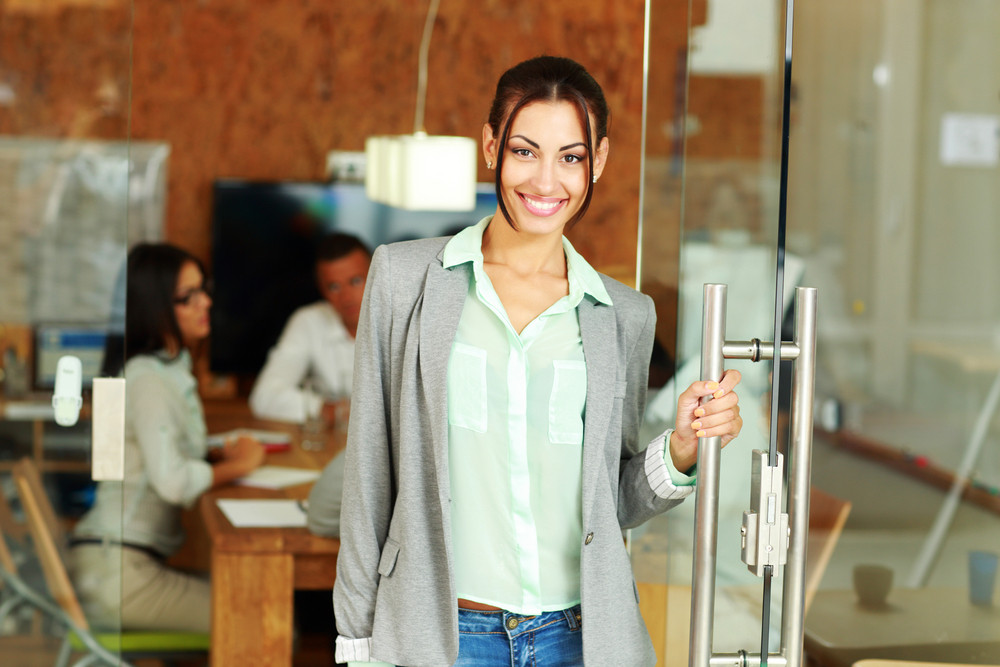 Happy cute businesswoman standing in front of colleagues